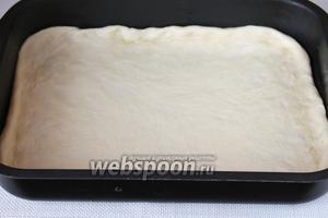 Когда тесто поднимется, раскатать 3/4 его объёма в пласт, который уложить на смазанный маслом противень.