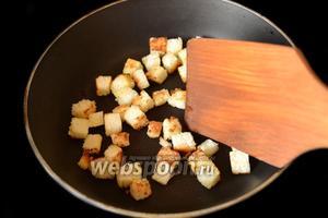 Ломтики батона, обрезав корки, нарезаем на кубики, орошаем оливковым маслом и зарумяниваем.