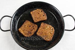 Подготовить тосты. Ломтики чёрного хлеба обжарить с двух сторон на оливковом масле.