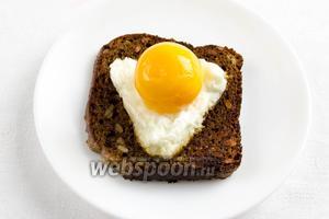 На поджаренный тост выложить белок, а сверху желток.