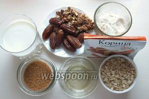 Для приготовления подготовьте необходимые ингредиенты: овсяные хлопья, рафинированное и дезодорированное растительное масло, коричневый сахар, кефир не жирный, грецкие орехи, финики, пшеничную муку, просеянную с солью и содой. Включите духовку на 180°C.