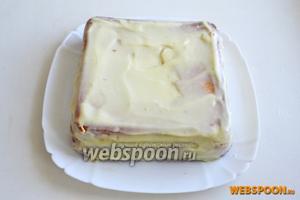 Обильно смажьте торт по бокам и сверху ганашем из белого шоколада.