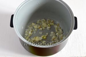 Лук порезать кубиками. В чашу мультиварки выложить лук и подсолнечное масло и включить режим «Выпечка». Готовить 5 минут при открытой крышке мультиварки (у меня мультиварка Polaris).