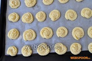 Выложить тесто в кондитерский  пакет и выдавить через насадку «звёздочка» на лист застеленный пекарской бумагой небольшие печенья.