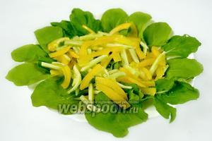 Смесь соломки из огурца и перца насыпать сверху салатных листьев.