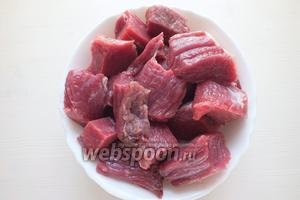 Очистите мясо от плёнок и лишнего жира. Нарежьте мясо крупными кусками, по 3-4 куска на порцию. Используйте для приготовления любую часть туши по желанию, например, мякоть с ноги или лопатки.