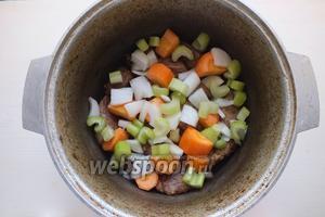 Нарежьте кусочками лук и сельдерей. Крупно нарежьте морковь и добавьте к мясу.