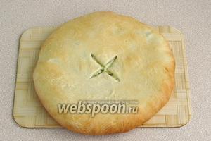 Тесто аккуратно раскатать ладонями, равномерно распределяя начинку. В центре пирога сделать надрез, чтобы выходил воздух.