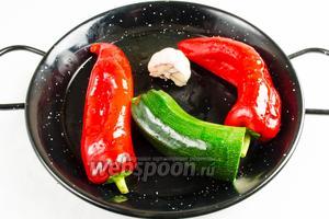 В первую очередь нужно запечь овощи. Для этого нужно смазать перцы и половину цукини (можно и целый плод использовать) оливковым маслом. У головки чеснока срезать край. Выложить овощи на сковороду и поставить в горячую духовку. Выпекать в режиме гриль 30 минут при температуре 220°C.