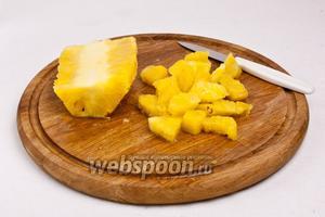 Срежьте колючую кожицу ананаса и нарежьте фрукт ломтиками толщиной чуть больше 1 см. Для коктейля нам достаточно половины ананаса (сердцевину не использовать, если у вас блендер недостаточно мощный).