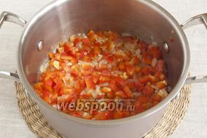Добавить очищенные и мелко нарезанные чеснок и сладкий перец. Обжаривать всё вместе несколько минут.