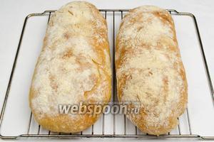 Готовые чиабатты вынуть. Выложить остывать на решетку. Нарезать хлеб лучше через час-полтора (очень мягкий). Подавать к обеду как бутерброды, смазать сливочным маслом.