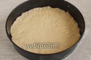 Форму застелить пергаментной бумагой, бока формы смазать маслом. Тесто ложкой выложить в форму, разровнять, придавить руками, чтобы получился равномерный слой теста.