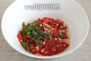 Добавить мелко нарезанные листья базилика. Чеснок почистить и как можно мельче нарезать, добавить к помидорам, положить каперсы.