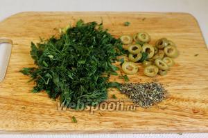 Часть оливок нарезать кружочками, измельчить зелень укропа и петрушки.