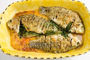 Форму с готовой рыбой аккуратно вынуть из духовки. Печёную зелень вынуть из брюшек рыбы.