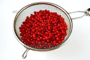 Промываем смородину, погружая сито в большую кастрюлю с водой. Погружение позволяет всплыть мелким веточкам и засохшим «носикам» ягод, которые трудно удалить под струей воды. Даём воде стечь, а ягодам подсохнуть, в это время кипятим воду.
