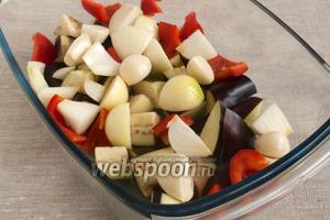 Добавить половину сладкого перца, очищенную от семян и нарезанную крупно. Лук и чеснок почистить, лук нарезать большими кусками, добавить в форму. Чесночные зубки поместить целиком.
