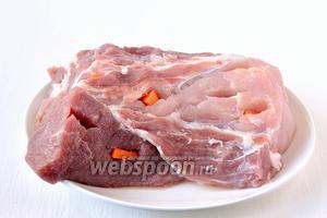 В мясе сделать надрезы острым ножом через каждые 10 см. В надрезы вставить морковь или чеснок.