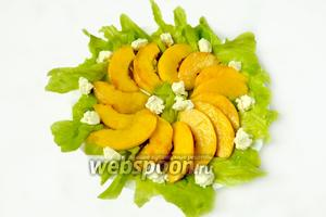 На тарелку рвём салатные листья, укладываем венком дольки нектарина, разбрасываем кусочки творожного сыра.