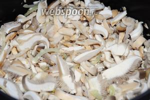 Добавьте к луку грибы, перемешайте и продолжайте жарить под крышкой, периодически помешивая.
