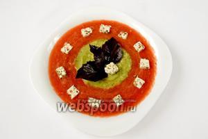Разливаем суп в тарелки следующим образом: сначала красную смесь, потом в центр — зелёную, стараясь, чтобы она не расплылась, сбрызгиваем оливковым маслом. По окружности кладём кубики брынзы, а в центр — листочки фиолетового базилика. Суп подаём без промедления.