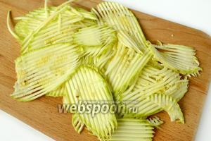 Вымытый кабачок нарезаем лентами с помощью овощечистки или фигурными пластинками на терке.