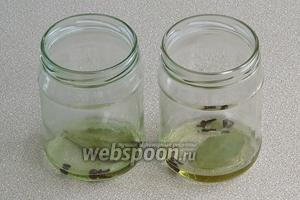 На дно стеклянных стерилизованных банок ёмкостью 0,5 л налить по 2–3 столовые ложки прокаленного и охлажденного подсолнечного масла и положить пряности.