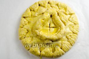 Смазать поверхность пирога желтком. Перетянуть бумагу с пирогом на противень. Поставить противень с пирогом в горячую духовку 180 °C. Выпекать в течение 40 минут.