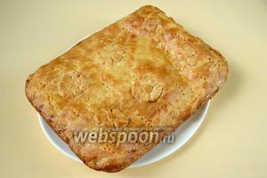 Извлекаем пирог из формы за края бумаги. Так как горячая картофельная начинка очень мягкая, пирог может деформироваться, поэтому и помогает бумага с широкими краями. Остужаем пирог на доске или большом плоском блюде. Тёплым его можно подать к обеду, а холодным к чаю.