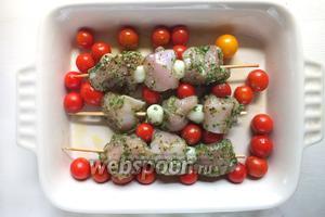 Насадите на шпажки промаринованные кусочки курицы, чередуя с луком и выложите шпажки в форму с помидорами. Запекайте примерно 20-25 минут. Примерно в середине приготовления шпажки нужно перевернуть на другой бок.