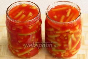 Горячим томатным пюре залить стерилизованные банки с фасолью.
