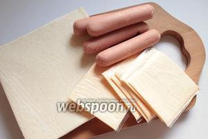 Для приготовления нам понадобится слоёное тесто бездрожжевое, 8 сосисок, 8 пластинок плавленного сыра и яйцо для смазывания. Оставить тесто размораживаться на полчаса.