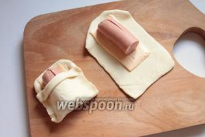 Подогнуть верхние уголки теста, накрыть сосиску нижней частью теста, придавая форму кармашка.