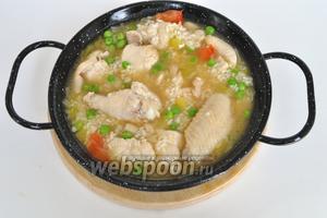 Далее добавляем рис и соль, раскладываем на порционные сковороды и заливаем куриным бульоном.