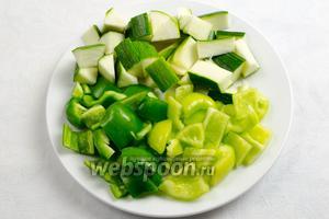 Овощи вымыть. Просушить. Нарезать на куски среднего размера цукини и перцы.