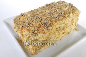 Обсыпать весь торт крошками бисквита и тёртой халвой, а сверху немного семян подсолнечника.