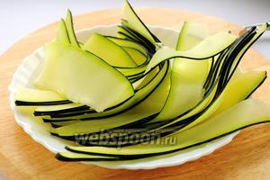 Кабачок шинкуем вдоль на тонкие пластины овощечисткой или овощерезкой.