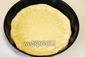 На смазанный противень или форму для пирога выложим тесто, прямо руками распределим его по всей поверхности. Слой должен быть около 1 см толщиной.