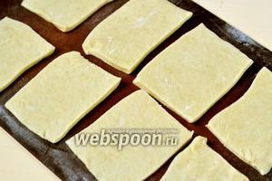 Заранее извлечённое из холодильника и согретое тесто раскатываем и нарезаем прямоугольниками.