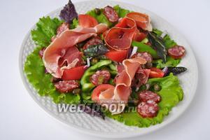 Выложим на тарелку листья салата и базилик, затем овощи, колбаски, поперчим. Теперь волнами — хамон, можно его просто порвать на кусочки.