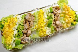 Выбрать широкий плоский салатник. Разложить по дну рваные куски салата. Ингредиенты разложить полосами, учитывая вкусовые качества и цвет.