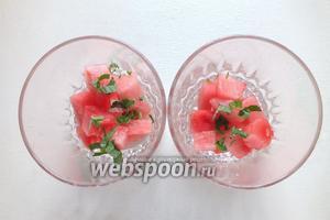 Выложите в порционную посуду часть кубиков арбуза, посыпав зеленью.