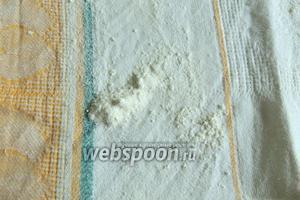 На кухонное полотенце насыпем немного муки и распределим по всей поверхности.