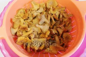Тем временем отваренные грибы откинуть на дуршлаг и промыть холодной водой.