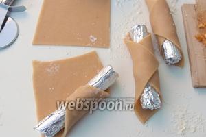 Раскатываем тесто на припудринном мукой рабочем месте в четырёхугольник. Затем режем на квадраты 8х8 и толщиной теста около 2 мм, можно тоньше. На формы паматываем тесто в трубочки, уложив формы на один из углов квадратов по диагонали.