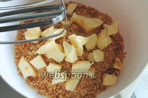 Печенье измельчим в крошку и добавим масло, нарезанное на малые куски. Перетрём до однородности руками или миксером.