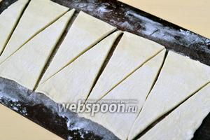 Заранее размороженное тесто раскатываем в одном направлении в длинную ленту шириной 16-18 см. Нарезаем тесто треугольниками.