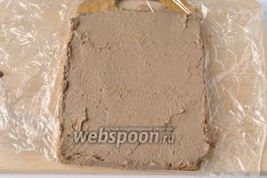 Доску застелить пищевой плёнкой, и ровным слоем выложить печень. Поместить в морозильник на 7-12 минут, что бы слой схватился и не продавливался начинкой.