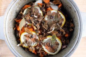 Добавьте в казан тонкие ломтики лимона, раздавленные ягоды можжевельника, лавровый лист, порезанные кусочками сухие грибы вместе с жидкостью.